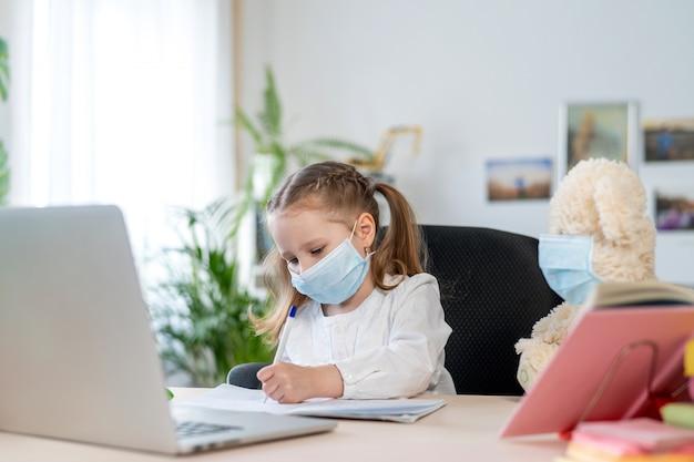 Menina na máscara, com ursinho de pelúcia, fazendo lição de casa, e-learning