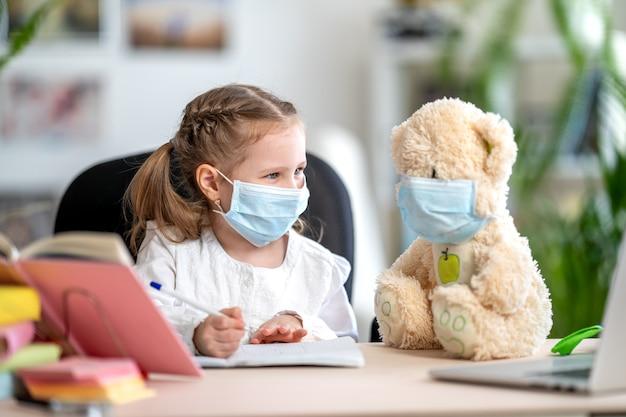 Menina na máscara, com ursinho de pelúcia, fazendo lição de casa. prevenção de coronavírus