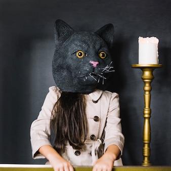 Menina na máscara de gato e vela