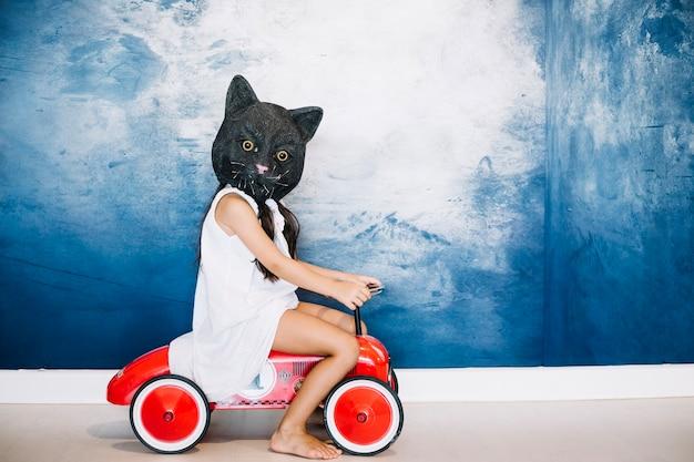 Menina na máscara de gato no carro