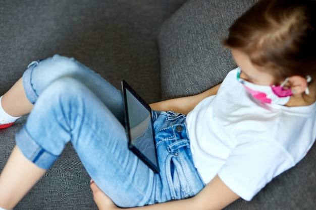 Menina na máscara de proteção usando, jogar tablet ou aprender com videochamada online