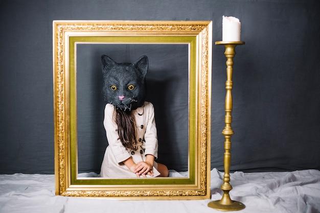Menina na máscara do gato atrás do quadro