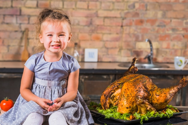 Menina na mesa com peru assado