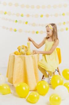 Menina na mesa rodeada por balões e limões