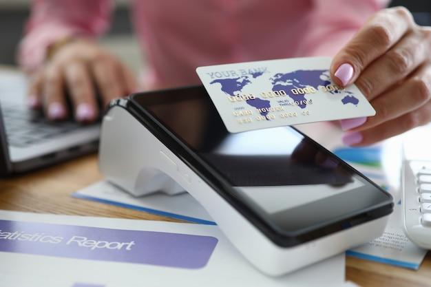 Menina na mesa tem cartão de crédito sobre o terminal do banco