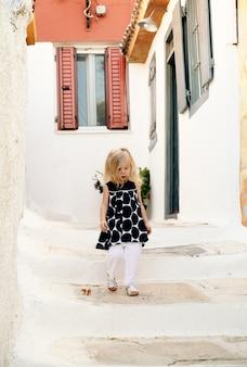 Menina na moda andando pelas ruas da grécia