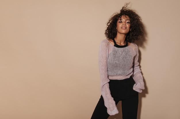 Menina na moda com cabelos cacheados fofos em um suéter rosa, blusa legal e calças pretas, olhando para a câmera na parede isolada.