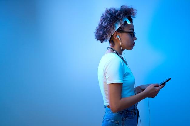 Menina na moda com cachos afro usa smartphone e fones de ouvido em um fundo de estúdio com espaço de cópia