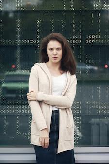 Menina na moda com verruga na bochecha, blusa de cor baunilha e saia jeans azul na janela reflexiva de fundo da loja.