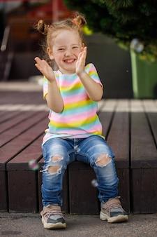 Menina na moda de jeans e camiseta colorida