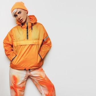 Menina na moda de urban outfit tomboy em uma roupa esportiva laranja brilhante