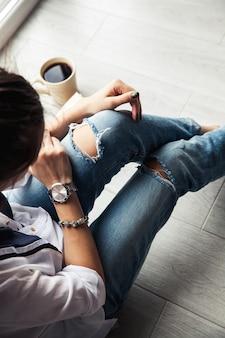 Menina na moda elegante com uma xícara de café e uma manicure verde em jeans.