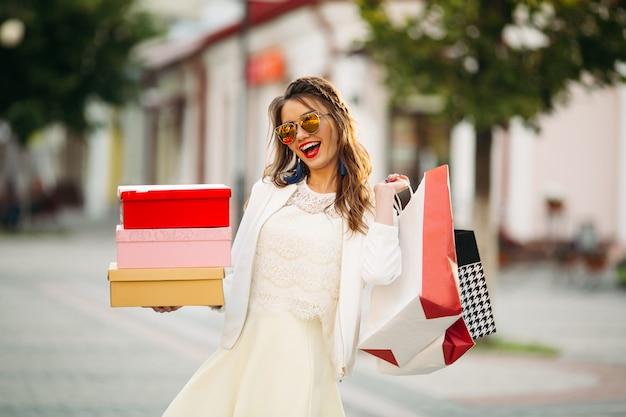 Menina na moda em óculos de sol com caixas de sapato e sacolas de compras em t