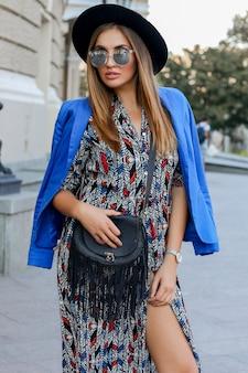 Menina na moda em roupa elegante de outono, caminhando durante as férias na europa. bolsa de couro elegante. jaqueta azul e chapéu preto.