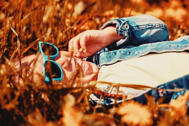 Menina na moda encontra-se na grama e ri. infância feliz. foto de alta qualidade