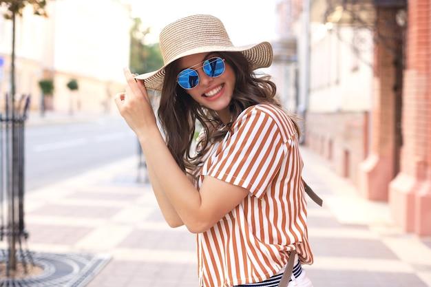 Menina na moda hippie sorridente posando na rua de verão da cidade, segurando o chapéu.