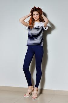 Menina na moda hipster brincando com mechas de cabelo pintadas em vermelho fogo. pernas longas em calças azuis apertadas, camiseta com listras, estilo de rua.