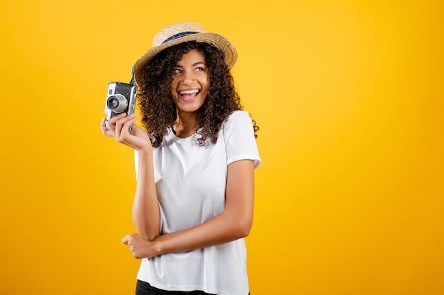 Menina na moda hipster preto com câmera vintage e chapéu isolado sobre amarelo