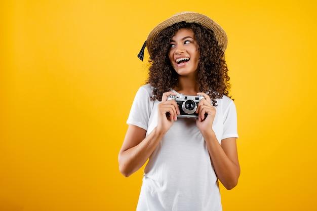 Menina na moda hipster preto com câmera vintage e chapéu isolado sobre amarelo Foto Premium