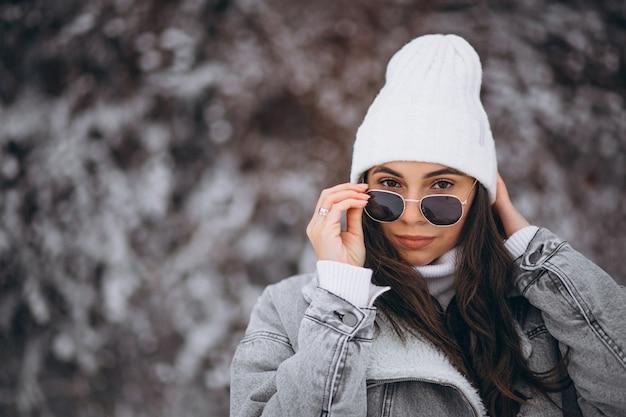 Menina na moda jovem em um parque de inverno