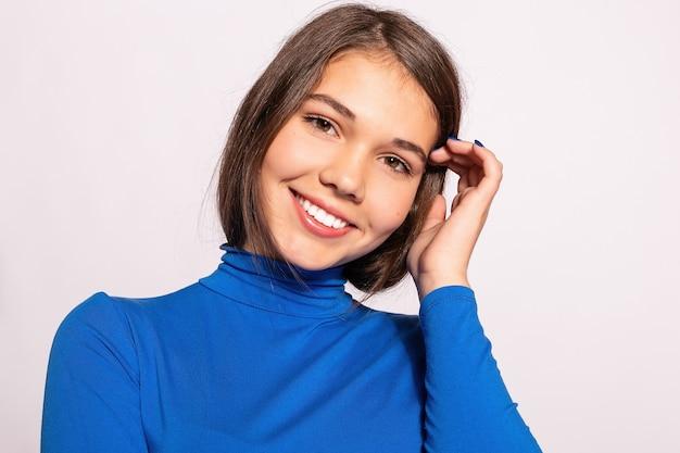Menina na moda linda hippie. foto de mulher bonita jovem positiva em meias azuis até o joelho com fundo branco. olha para a câmera. olhando para a câmera e sorrindo