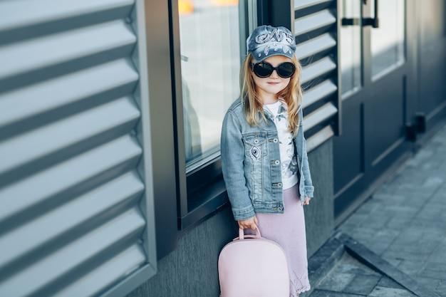 Menina na moda loira de boné jeans e jaqueta com bolsa rosa