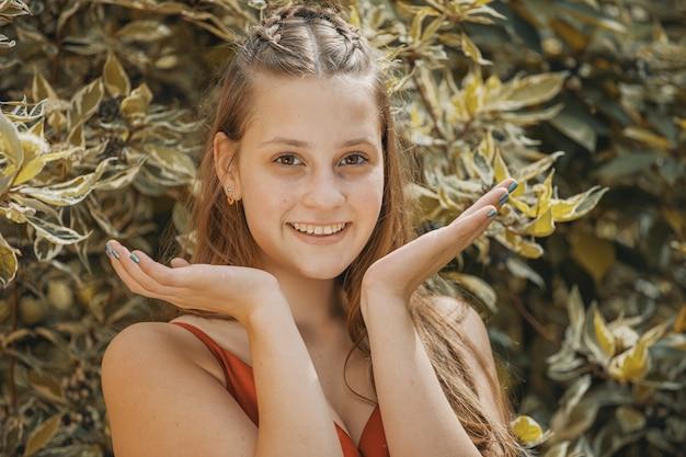 Menina na natureza com as palmas das mãos no rosto e sorri