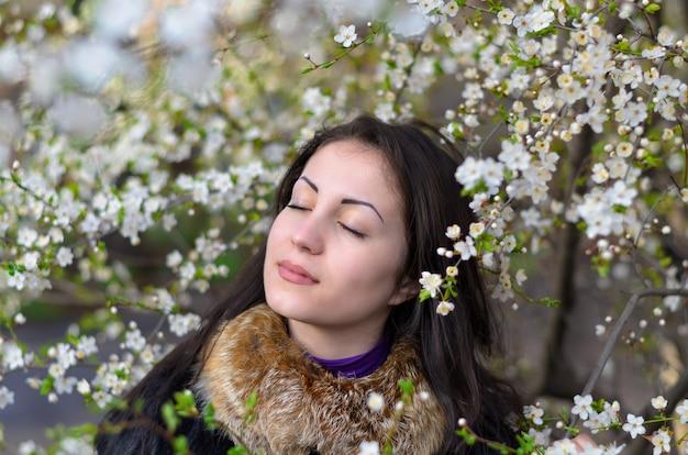 Menina na natureza entre árvores floridas