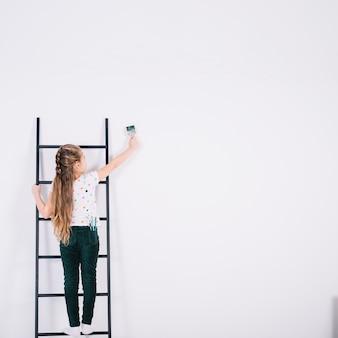 Menina na parede de pintura de escada