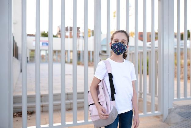 Menina na porta da escola com máscara
