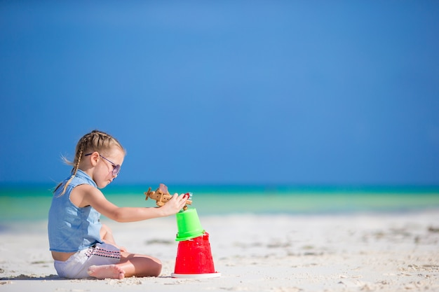 Menina na praia branca tropical fazendo castelo de areia