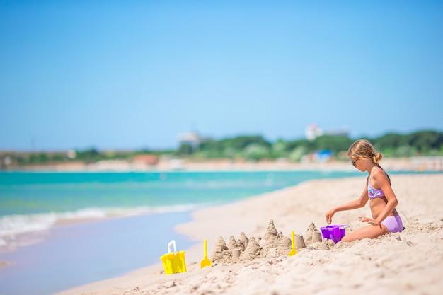 Menina na praia branca tropical, fazendo o castelo de areia
