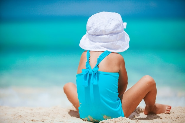 Menina na praia tropical branca fazendo castelo de areia