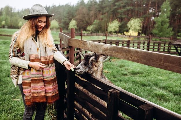 Menina na roupa com os padrões étnicos que levantam contra o da cerca na fazenda velha, vida rural.