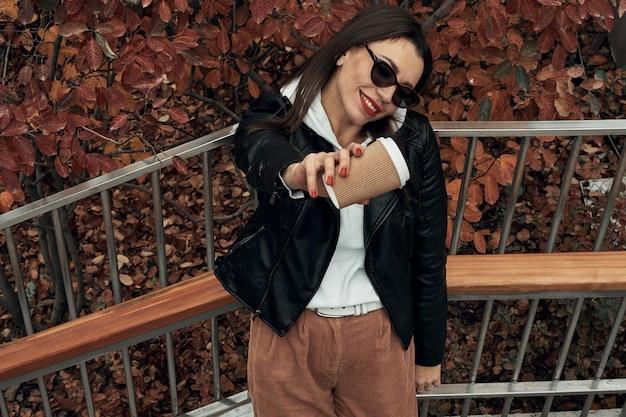 Menina na rua com um copo de papel descartável. leve comida, caminhe pela cidade.