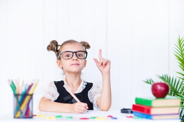 Menina na sala de aula com lápis e livros