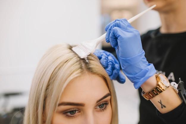 Menina na sala de cabeleireiro com procedimento de colorir