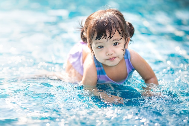 Menina nadando na piscina ao ar livre e divirta-se