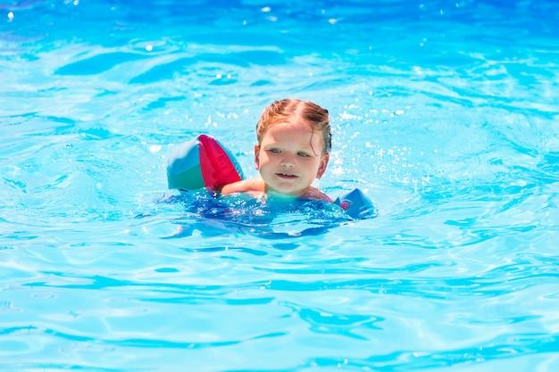 Menina nadando na piscina com mangas flutuadores