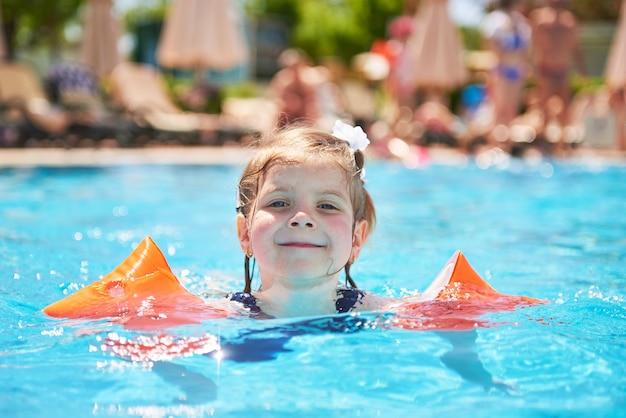 Menina nadando na piscina em braçadeiras em um dia quente de verão. férias em família em resort tropical
