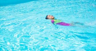 Menina nadando na piscina, flutuar na água
