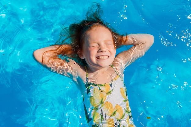 Menina nadando na piscina no verão