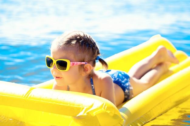 Menina nadando no colchão de praia inflável.