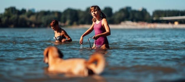 Menina nadando no rio com seu cachorro