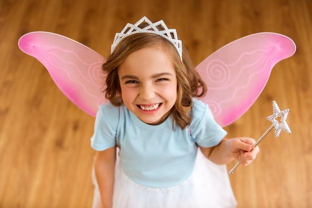 Menina nas asas cor-de-rosa que guardam uma varinha mágica.