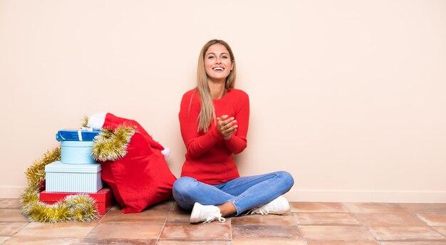 Menina nas férias de natal, sentada no chão aplaudindo