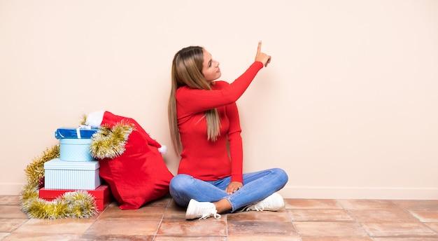 Menina nas férias de natal, sentada no chão, apontando para trás com o dedo indicador