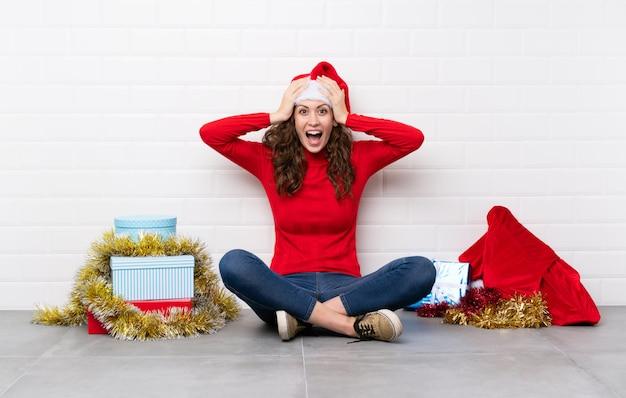 Menina nas férias de natal, sentada no chão com expressão facial de surpresa