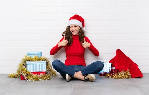 Menina nas férias de natal, sentada no chão, dando um polegar para cima gesto