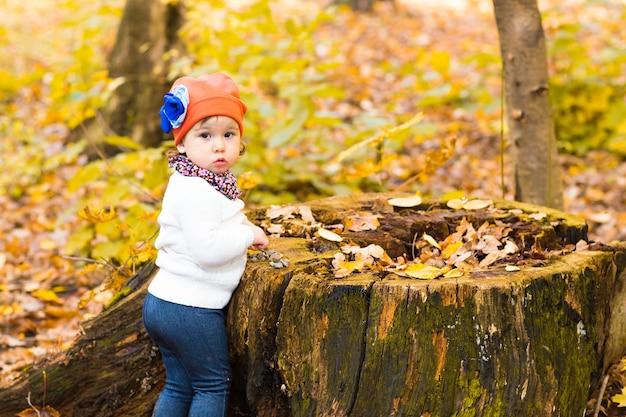 Menina nas folhas de outono. linda garota sentada no toco na floresta de outono.